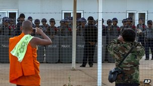 A protesting Buddhist monk and a man take pictures of Burmese police at the Letpadaung mine, Monywa, 28 November 2012