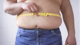 Overweight man measuring his waist
