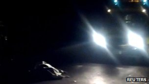 A still image from amateur camera phone video shows a covered body in Weybridge with a police car standing nearby, 10 November