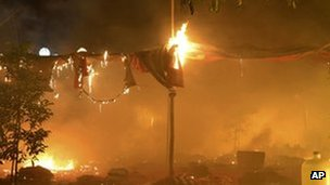 An encampment occupied by protesters burns following a crackdown by security forces near the copper mine in town of Monywa, 29 November 2012