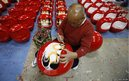 Japanese craftsman Sumikazu Nakata adds the final touches on a Daruma doll