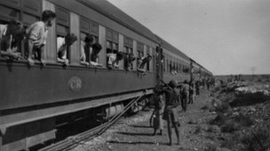 Aboriginal people pass food to the train in the desert