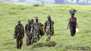 M23 rebel fighters walk up a hill in Mushake, 70km (40 miles) west of Goma 