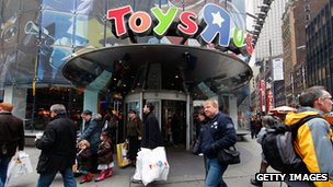 Shoppers walk outside of a toy store.