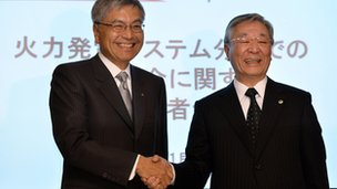 Mitsubishi Heavy Industries president Hideaki Omiya (L) shakes hands with Hitachi president Hiroaki Nakanishi at a press conference