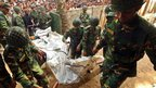 Bangladeshi soldiers carry the bodies from the factory