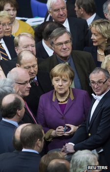 German Chancellor Angela Merkel stands amid MPs before the vote in the Bundestag in Berlin, 30 November