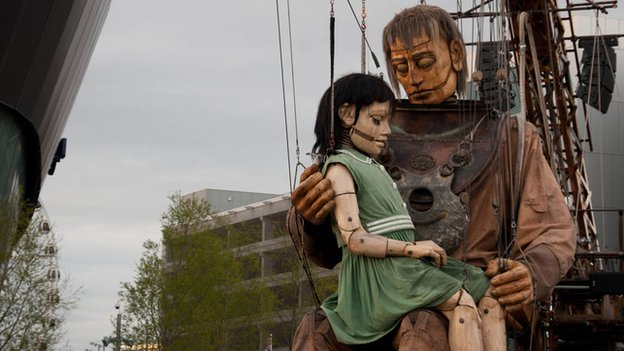 A giant marionette of a girl sits in the lap of a giant diver