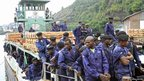 Congolese national police officers arrive on a ferry at a port at Lake Kivu