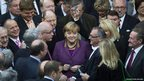 German Chancellor Angela Merkel, centre, and fellow parliamentarians 