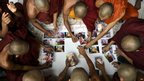 Buddhist monks stick pictures of monks who were injured 