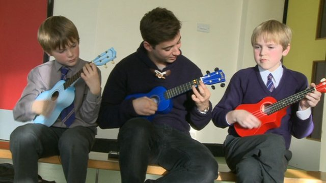 Ricky playing the ukulele with two kids