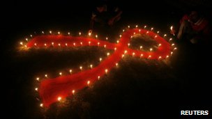 Red ribbon symbol and candles in India for World Aids Day