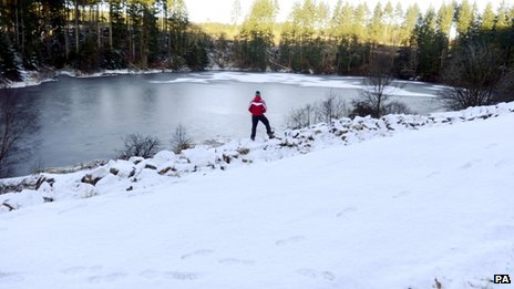 A person looks at ice while surrounded by snow at Kielder Water, Northumberland