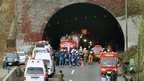 Police officers and fire fighters gather at the entrance of the Sasago Tunnel