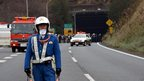 A policeman stands guard in front of emergency service vehicles on the road leading to the entrance of the collapsed Sasago tunnel