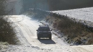 A vehicle drives along a snow covered road in the Scottish Borders