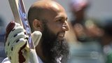 South Africa's Hashim Amla raises his bat after reaching a century