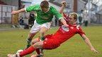 Cliftonville's Stephen Garrett is tackled by Portadown defender Ross Redman during the Irish Premiership clash at Shamrock Park