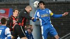 Crusaders skipper Colin Coates contests a high ball with Dungannon defender Emmett Friars