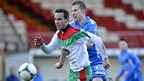 Glentoran striker Andrew Waterworth gets to the ball before Ballinamallard player Leo Carters at the Oval