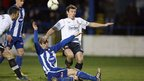 Coleraine's John Watt slides in to challenge Kyle Neill of Glenavon