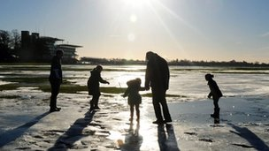 People walk on frozen flood water at York Racecourse, England