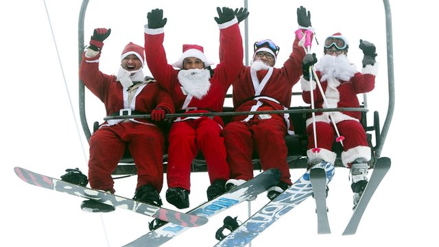 People dressed as Santa on a ski lift.