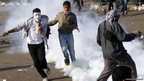 Demonstrators run away from tear gas 