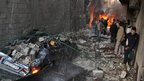 Syrian men inspect the scene of a car bomb explosion 