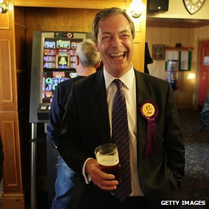 Nigel Farage in a pub, holding a pint