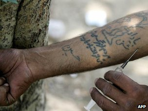 An Iranian drug addict injects himself with heroin in a park in Tehran (2006)