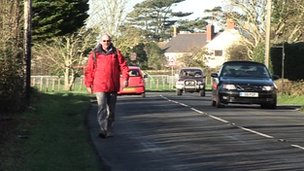 Walker on Isle of Wight road without footpath