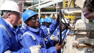 Ghanaian President John Atta Mills (second from right) turns a valve to start Ghana's first oil production at the FPSO Kwame Nkrumah oil rig, at the Jubilee field, on 15 December 2010.
