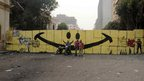 Men pose in front of graffiti on Qasr al-Aini Street, Cairo