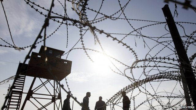 Turkish workers work to reinforce the border fence between the northern Syrian town of Ras al-Ain and the Turkish border town of Ceylanpinar