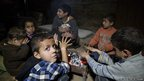 On a cold November night, Yousef Khodor, 6, and his siblings warm themselves by a fire inside a former sheep shed in northern Lebanon where they now live. 