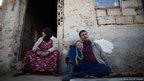 Ahmed Khodor sits with his sister outside a former sheep shed in northern Lebanon where his family now lives.