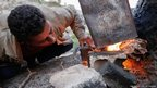 Ahmed Khodor, 46, builds a fire outside a former sheep shed in northern Lebanon where his family of nine now lives.