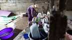 Nada Khodor makes coffee on the basic gas stove her family use for preparing hot food inside the former sheep shed in northern Lebanon in which they now live.