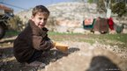 Hammoudi Khodor, 2, plays outside the abandoned sheep shed in northern Lebanon in which his family now live