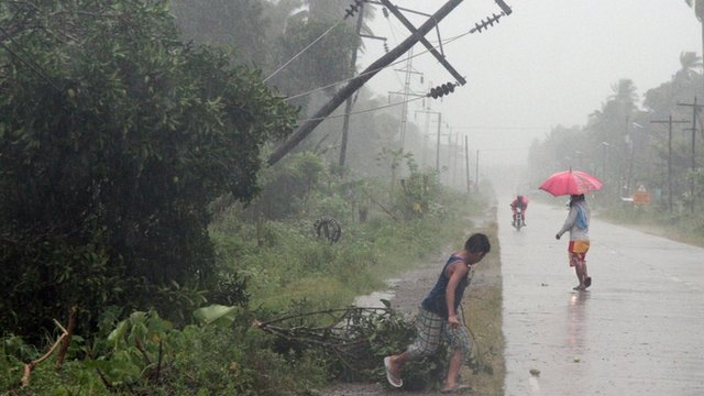 Residents brave heavy rains next to a tilted electric post after Typhoon Bophal hit the city of Tagum