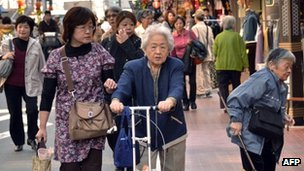 Elderly people walk down a busy street
