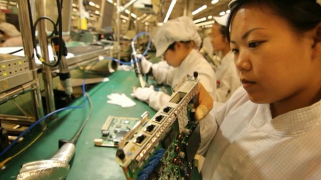 Factory worker checks component