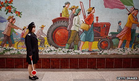 Official stands beside a mural in a Pyonyang metro