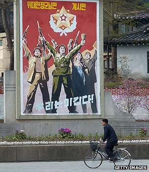 Man cycles past propaganda poster in Pyongyang