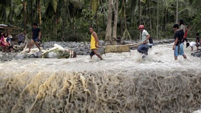 Residents carry the body of victim after flash floods brought by Typhoon Bopha swept New Bataan town in Compostela Valley