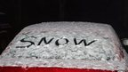 Car with &quot;snow&quot; written in snow on its rear windscreen