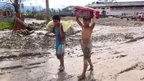 Children carrying belongings along a muddy road in New Bataan in Compostela Valley