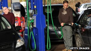 Men fill up cars with petrol